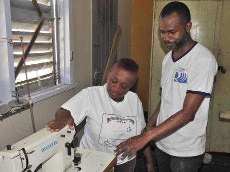 Karen Brown (left), president of the Jamaica Association for Persons with Physical Disabilities (JAPPD) showing one of the old sewing machines at the facility with Gareth Manning, president of the Rotary Club of Trafalgar New Heights recently.